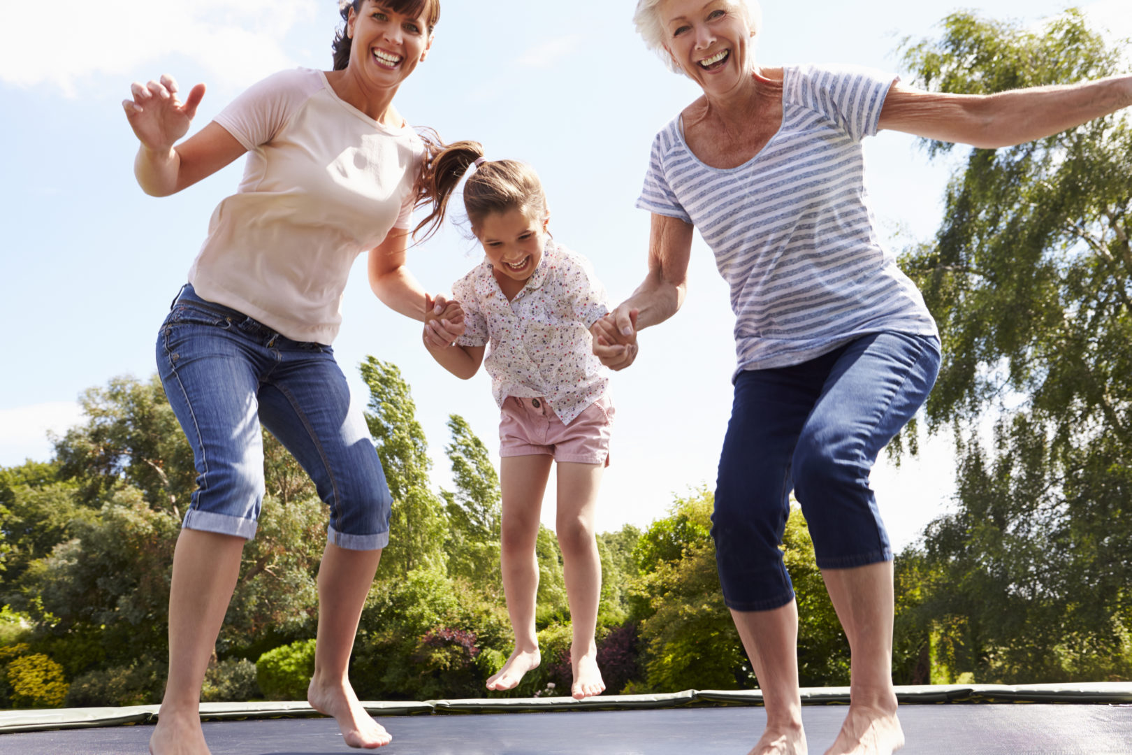 grandmother with arthritis jumping on trampoline with family