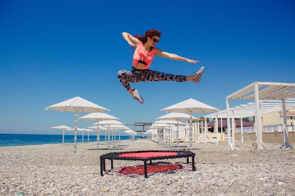 A slim athletic girl with dreadlocks jumping on a fitness trampoline outdoors on a pebble beach by the sea
