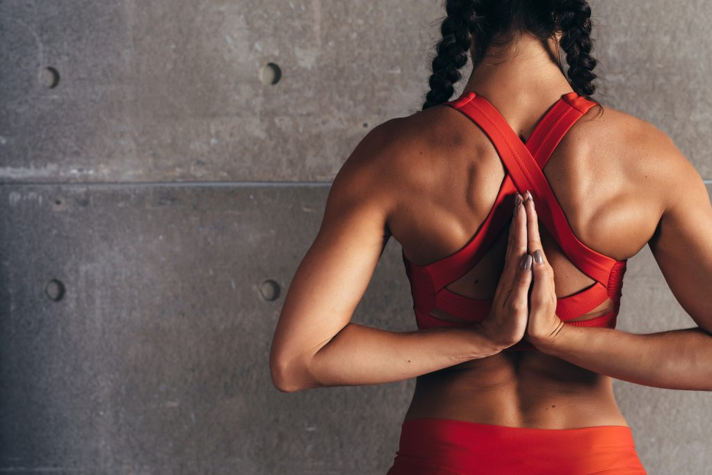 Close up fit woman with arms behind back doing stretching exercises
