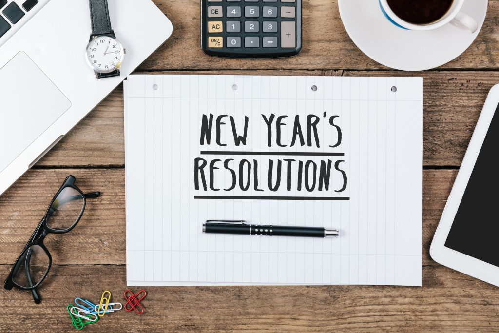 "note with ""new years resolution"" text, Office desk with electronic devices, computer and paper, wood table from above, concept image for blog title or header image."