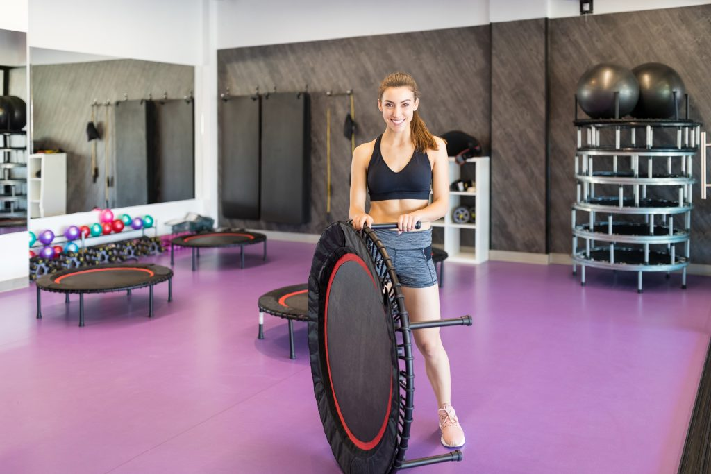 Smiling Caucasian woman in sportswear holding mini trampoline in gym